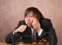 Il giovane mangia i mandarini Fotografie Stock