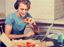 Il giovane mangia la pizza facendo uso di Internet praticante il surfing del computer portatile Immagine Stock Libera da Diritti
