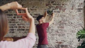 Il giovane marito sta scegliendo il posto sul muro di mattoni per appendere il photograpt mentre la sua moglie sta facendo la str archivi video