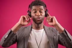 Il giovane maschio africano che indossa le cuffie è pazzo a musica fotografia stock libera da diritti