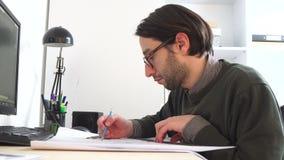 Il giovane maschio dell'architetto che lavora nell'ufficio sullo scrittorio, tipi su un computer portatile, blueprints mettere su stock footage
