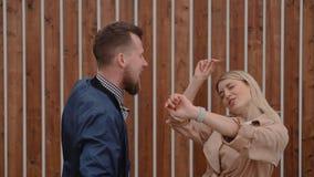 Il giovane maschio due e la gente femminile stanno ballando all'aperto vicino alla parete di legno archivi video