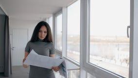 Il giovane mediatore della donna di affari dell'avvocato sta leggendo il business plan, stante nell'ufficio moderno stock footage