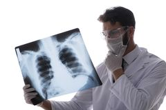 Il giovane medico che esamina le immagini dei raggi x isolate su bianco Fotografia Stock