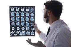 Il giovane medico che esamina le immagini dei raggi x isolate su bianco Immagini Stock Libere da Diritti