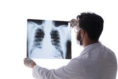 Il giovane medico che esamina le immagini dei raggi x isolate su bianco Fotografia Stock Libera da Diritti