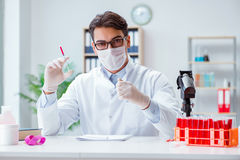Il giovane medico che lavora nel laboratorio con il microscopio Fotografia Stock