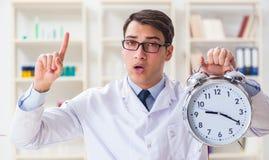 Il giovane medico con la sveglia nella clinica dell'ufficio Fotografia Stock Libera da Diritti