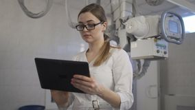 Il giovane medico controlla la diagnosi sulla compressa Macchina di raggi x video d archivio