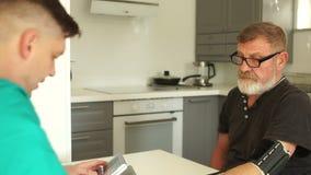 Il giovane medico o infermiere misura la pressione sanguigna di un anziano nella sua casa, in cucina Emergenza ambulanza stock footage