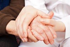 Il giovane medico tiene le mani anziane della donna Fotografie Stock Libere da Diritti
