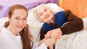 Il giovane medico tiene le mani anziane della donna Immagine Stock