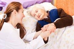 Il giovane medico tiene le mani anziane della donna Immagine Stock Libera da Diritti