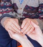 Il giovane medico tiene le mani dell'uomo anziano Fotografia Stock Libera da Diritti
