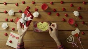 Il giovane mette il biglietto di S. Valentino di carta nella scatola attuale, vista superiore stock footage