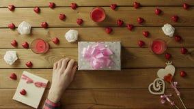 Il giovane mette il biglietto di S. Valentino sulla scatola attuale, vista superiore archivi video