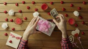 Il giovane mette il denaro contante nel contenitore di regalo come presente di festa, vista superiore archivi video