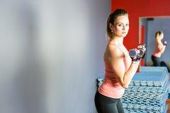 Il giovane mette in mostra la donna sexy di forma fisica con le teste di legno che posano sul fondo della parete Immagine Stock Libera da Diritti