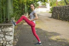 Il giovane mette in mostra la ragazza durante l'allenamento nel parco Forma fisica Fotografie Stock Libere da Diritti