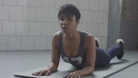 Il giovane misura ed il tono sulla menzogne della donna rilassata ha un resto durante il suo allenamento di forma fisica con gli  Fotografie Stock
