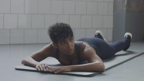 Il giovane misura ed il tono sulla menzogne della donna rilassata ha un resto durante il suo allenamento di forma fisica con gli  Fotografia Stock Libera da Diritti