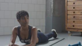 Il giovane misura ed il tono sulla menzogne della donna rilassata ha un resto durante il suo allenamento di forma fisica con gli  Fotografie Stock Libere da Diritti