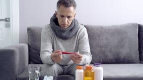 Il giovane misura la temperatura che si siede sul sofà nella casa Sensibilità maschio infelice durante un virus o il freddo archivi video