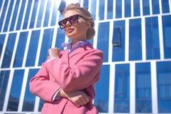 Il giovane modello in cappotto rosa è davanti alla costruzione magnifica fotografie stock