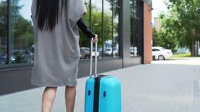Il giovane modello sta camminando con una fine della valigia su archivi video