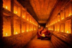 Il giovane monaco buddista sta leggendo un libro con luce dalla candela fotografie stock