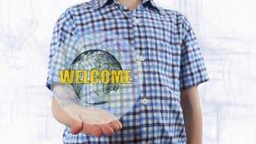 Il giovane mostra un ologramma del benvenuto del testo e del pianeta Terra Fotografia Stock Libera da Diritti