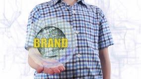 Il giovane mostra un ologramma della marca del testo e del pianeta Terra archivi video