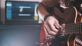 Il giovane musicista compone e registra la colonna sonora che gioca la chitarra facendo uso del computer e della tastiera Fotografie Stock Libere da Diritti