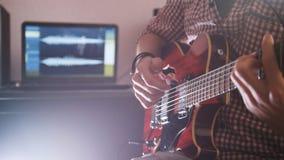 Il giovane musicista maschio compone e registra la colonna sonora che gioca la chitarra facendo uso del computer Fotografia Stock Libera da Diritti