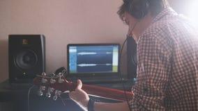Il giovane musicista maschio compone e registra la colonna sonora che gioca la chitarra facendo uso del computer Immagini Stock Libere da Diritti