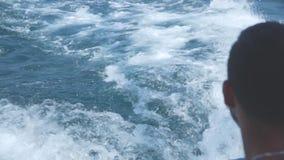 Il giovane naviga su un yacht in un mare non calmo ed esamina una nave sull'orizzonte video d archivio