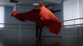 Il giovane nel corridoio di ripetizione Prova il ballo per la dichiarazione Per mezzo di tessuto rosso fa le rotazioni tessuto stock footage