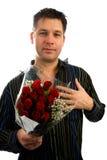 Il giovane nell'amore sta dando le rose rosse Immagine Stock Libera da Diritti