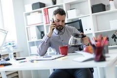 Il giovane nell'ufficio sta sedendosi alla tavola, sta parlando sul telefono e sta esaminando la caffettiera immagine stock libera da diritti