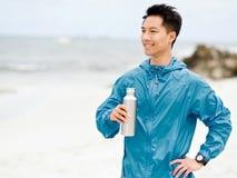 Il giovane nello sport copre l'acqua potabile dopo l'allenamento sulla spiaggia Fotografia Stock