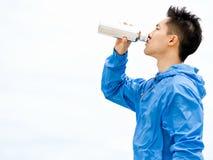 Il giovane nello sport copre l'acqua potabile dopo l'allenamento sulla spiaggia Fotografie Stock