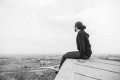 Il giovane non identificato di vista laterale in abbigliamento casual e vetri si siede sull'alta roccia ed esamina il bello deser Immagini Stock Libere da Diritti