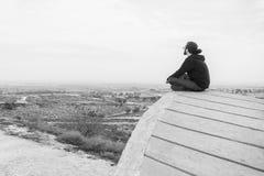 Il giovane non identificato di vista laterale in abbigliamento casual e vetri si siede sull'alta roccia ed esamina il bello deser Fotografie Stock