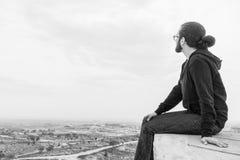 Il giovane non identificato di vista laterale in abbigliamento casual e vetri si siede sull'alta roccia ed esamina il bello deser Fotografie Stock Libere da Diritti