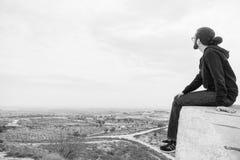 Il giovane non identificato di vista laterale in abbigliamento casual e vetri si siede sull'alta roccia ed esamina il bello deser Fotografia Stock Libera da Diritti