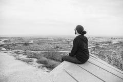 Il giovane non identificato di vista laterale in abbigliamento casual e vetri si siede sull'alta roccia ed esamina il bello deser Fotografia Stock
