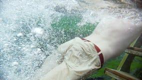 Il giovane nuota alle scale underwater nel chiaro lago blu archivi video