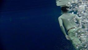 Il giovane nuota underwater in chiaro il lago blu archivi video