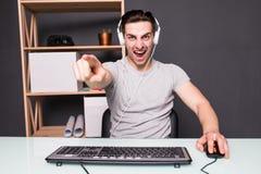 Il giovane o il pirata informatico in cuffia avricolare ed occhiali con il computer del pc che gioca il gioco e che scorre il vid Fotografia Stock