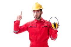Il giovane operaio con rumore che annulla le cuffie su bianco Fotografie Stock